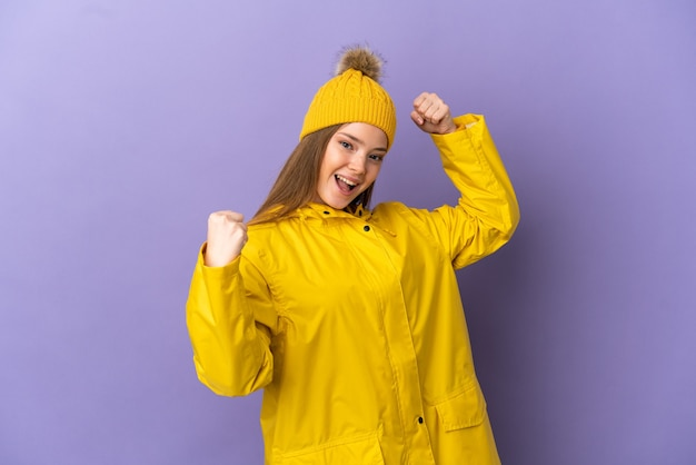 Teenager-mädchen, das einen regendichten mantel über isoliertem lila hintergrund trägt und einen sieg feiert