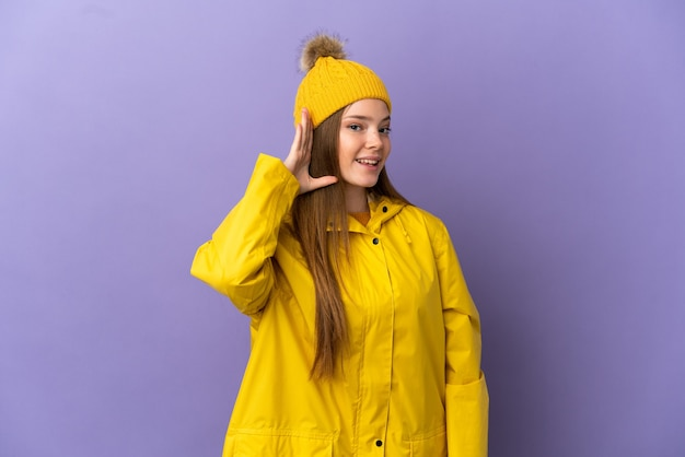 Teenager-mädchen, das einen regendichten mantel über isoliertem lila hintergrund trägt und etwas hört, indem es die hand auf das ohr legt