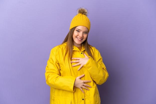 Teenager-mädchen, das einen regendichten mantel über isoliertem lila hintergrund trägt und viel lächelt