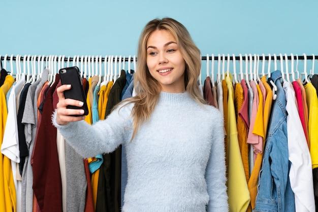 Teenager-mädchen, das einige kleider an der blauen wand kauft, die ein selfie machen