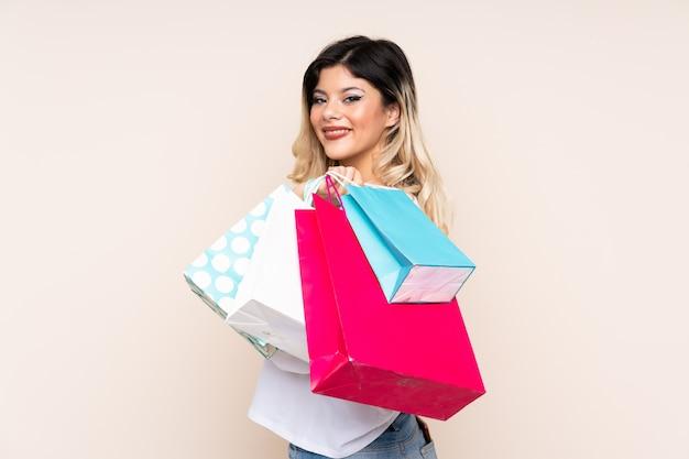 Teenager-mädchen, das einkaufstaschen hält und lächelt