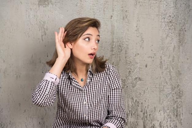 Teenager-mädchen, das etwas hört, indem man hand auf das ohr legt