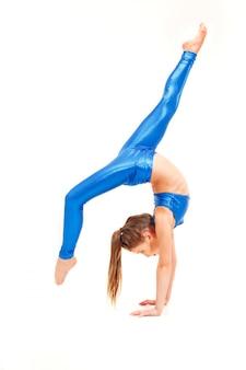 Teenager-mädchen, das gymnastikübungen lokalisiert auf weiß macht