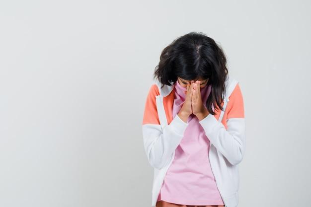 Teenager-mädchen, das hände über ihrem gesicht in jacke, hemd zusammenhält und beunruhigt aussieht.