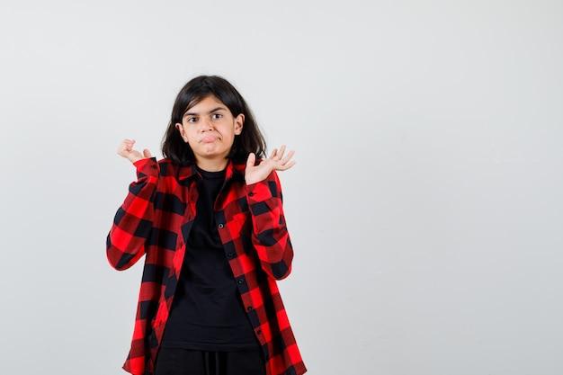 Teenager-mädchen, das hilflose geste im t-shirt, kariertem hemd zeigt und vorsichtig aussieht, vorderansicht.