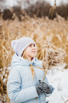 Teenager-mädchen, das im winter im feld geht