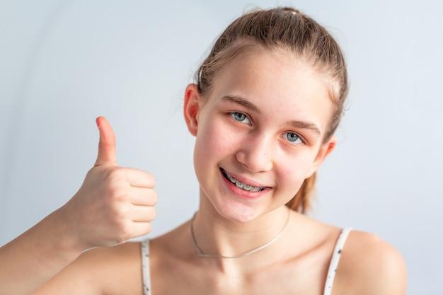 Teenager-mädchen, das in kieferorthopädischen klammern lächelt, die daumen oben zeigen. mädchen mit zahnspangen. kieferorthopädische behandlung.