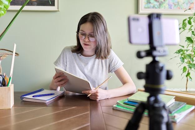 Teenager-mädchen, das online mit smartphone studiert, frau, die zu hause mit schulbüchern am tisch sitzt und bei videokonferenzen zuhört. fernstudium, e-learning, technologie, bildung, jugendliche