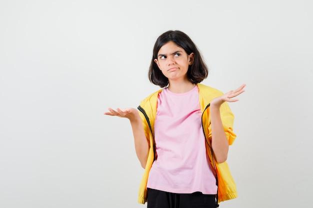 Teenager-mädchen, das palmen in gelbem trainingsanzug, t-shirt ausbreitet und düster aussieht, vorderansicht.
