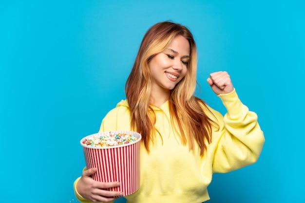 Teenager-mädchen, das popcorn über isoliertem blauem hintergrund hält und einen sieg feiert