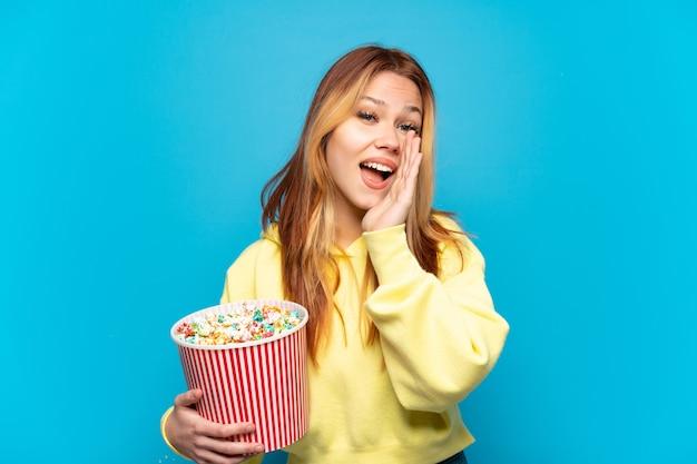 Teenager-mädchen, das popcorn über isoliertem blauem hintergrund hält und mit weit geöffnetem mund schreit