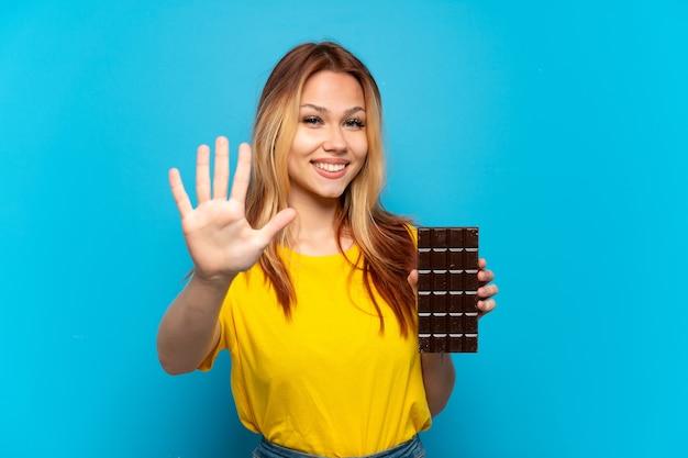 Teenager-mädchen, das schokolade über isoliertem blauem hintergrund hält und fünf mit den fingern zählt