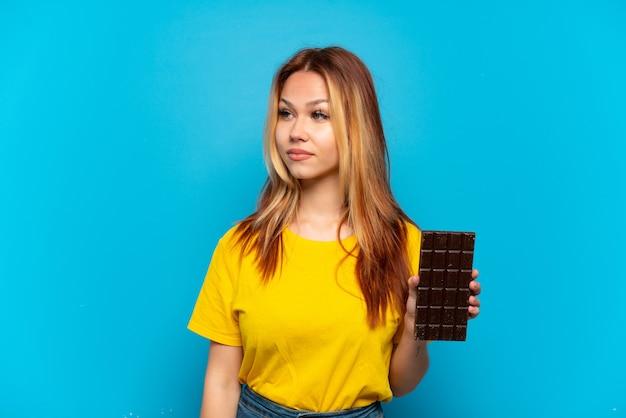 Teenager-mädchen, das schokolade über isoliertem blauem hintergrund hält und zur seite schaut
