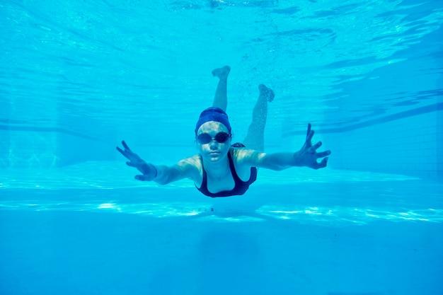 Teenager-mädchen, das unter wasser im pool schwimmt