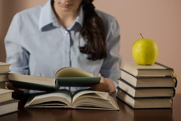 Teenager-mädchen, das viele bücher liest