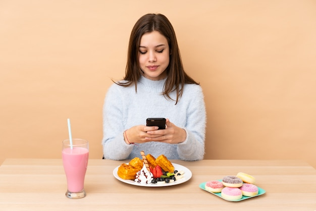 Teenager-mädchen, das waffeln auf beige wand isst, die eine nachricht mit dem handy sendet