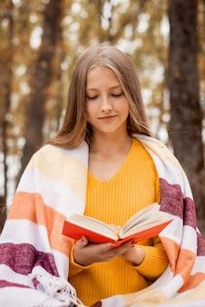 Teenager-mädchen, das warmes plaid trägt, das im park sitzt und einen roman liest