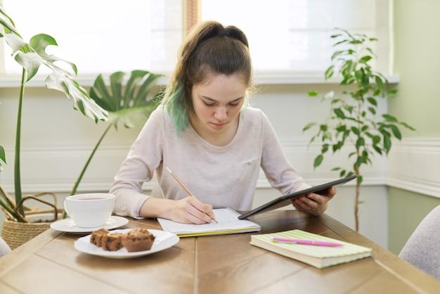 Teenager-mädchen, das zu hause studiert, junger student, der am tisch mit digitalem tablet sitzt, schulhefte, lehrbücher. fernunterricht online, technologie, bildungskonzept