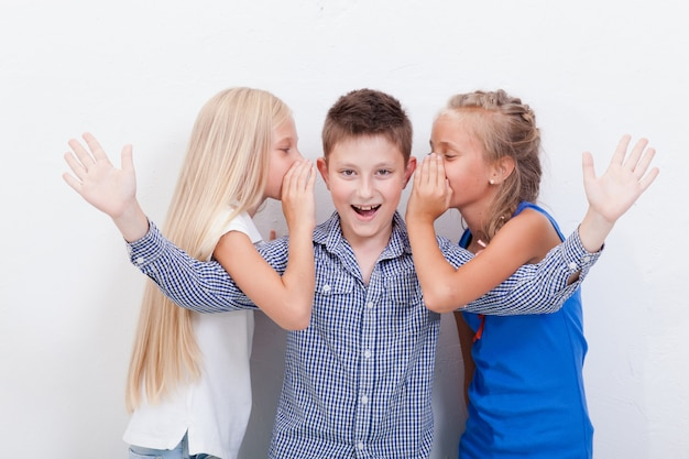 Teenager-mädchen, die in den ohren eines geheimen jugendlichen jungen auf weißer wand flüstern