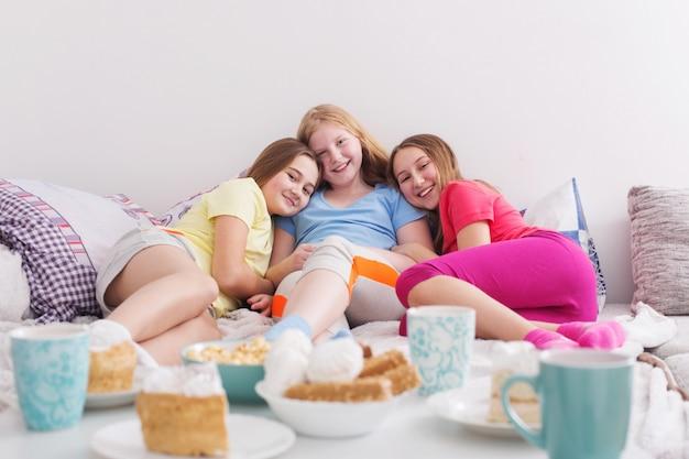 Teenager-mädchen, die tee trinken und süßigkeiten zu hause essen