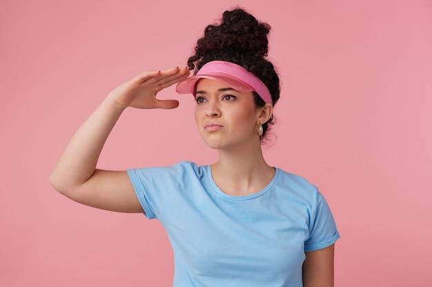 Teenager-mädchen, ernsthafte frau mit dunklem lockigem haar brötchen. trägt rosa visier, ohrringe und blaues t-shirt. hat sich geschminkt. schauen sie mit der handfläche über den augen in die ferne
