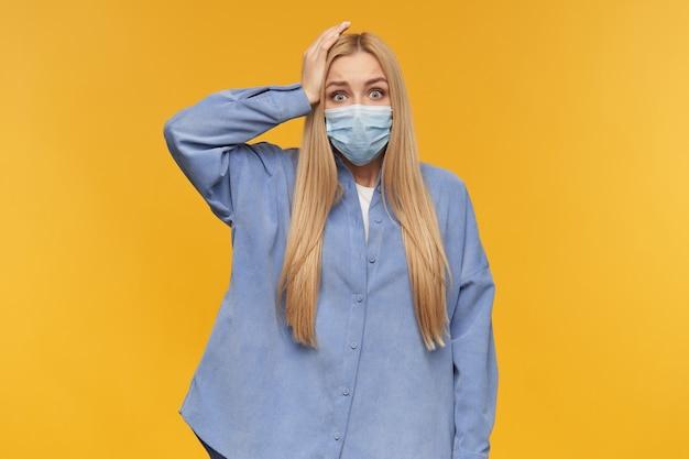 Teenager-mädchen, glücklich aussehende frau mit blonden langen haaren hält ihre hand auf dem kopf mit einer gruseligen grimasse. tragen des blauen hemdes und der medizinischen gesichtsmaske. menschen- und emotionskonzept.