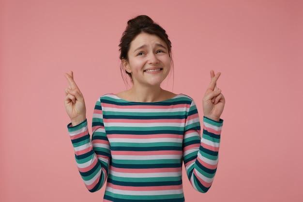 Teenager-mädchen, glücklich aussehende frau mit brünetten haaren und brötchen. gestreifte bluse tragen und sich mit daumendrücken etwas wünschen. emotionales konzept. stehen sie isoliert über einer pastellrosa wand