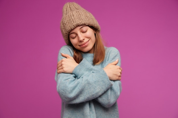 Teenager-mädchen, glücklich aussehende frau mit brünetten langen haaren. trägt einen blauen pullover und eine strickmütze. umarme sie selbst, fühle mich warm und gemütlich über lila wand