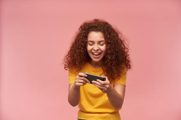 Teenager-mädchen, glücklich aussehende frau mit dem gelockten ingwerhaar, das gelbes t-shirt trägt