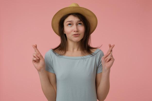 Teenager-mädchen, glücklich aussehende frau mit langen brünetten haaren. trägt ein bläuliches t-shirt und einen hut. aufblicken und etwas wünschen, daumen drücken. stehen sie isoliert über einer pastellrosa wand