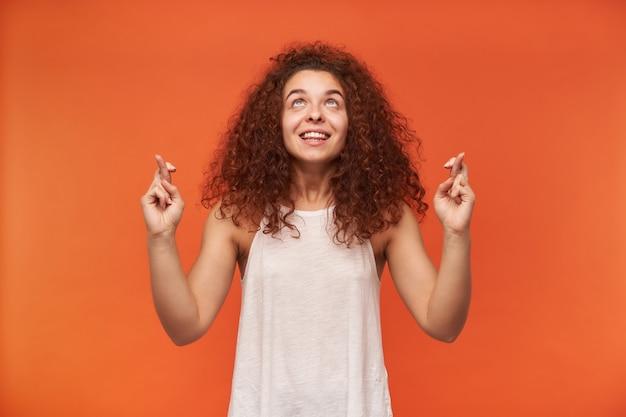 Teenager-mädchen, glücklich aussehende frau mit lockigem ingwerhaar. tragen einer weißen schulterfreien bluse. drückt die daumen und wünscht sich etwas. beobachtung im kopierraum, isoliert über der orangefarbenen wand