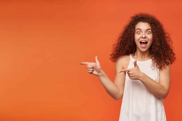 Teenager-mädchen, glücklich aussehende, fröhliche frau mit lockigem ingwerhaar. tragen einer weißen schulterfreien bluse. zeigt nach links auf den kopierbereich, isoliert über der orangefarbenen wand