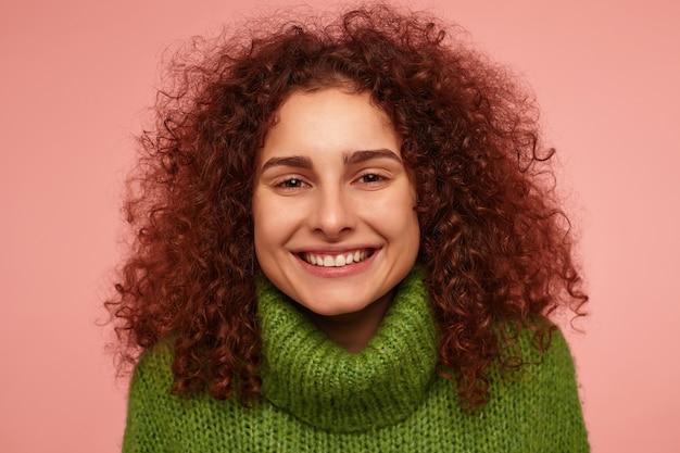 Teenager-mädchen, glücklich aussehende rothaarigefrau mit dem lockigen haar. tragen sie einen grünen rollkragenpullover und ein fuchsiges lächeln. isoliert, nahaufnahme über pastellrosa wand
