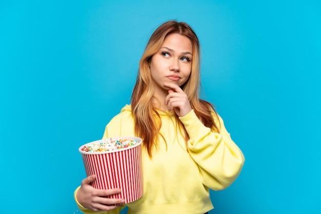 Teenager-mädchen hält popcorn über isoliertem blauem hintergrund und schaut nach oben