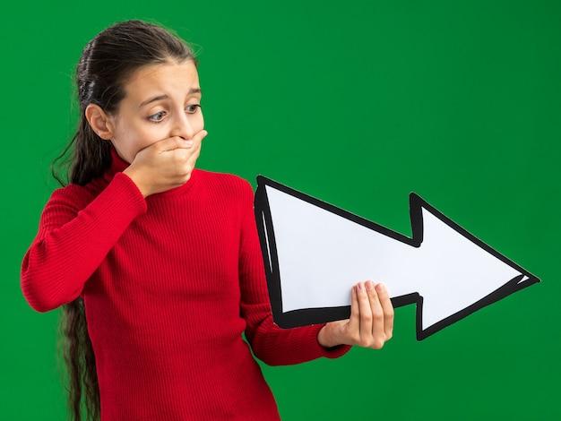 Teenager-mädchen hält und schaut auf die pfeilmarkierung, die auf die seite zeigt und die hand auf dem mund hält, isoliert auf grüner wand
