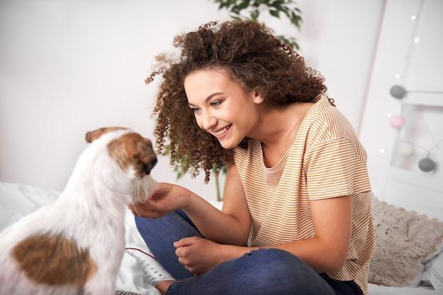 Teenager-mädchen hat spaß mit ihrem hund im schlafzimmer