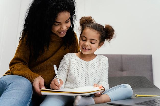 Teenager-mädchen hilft schwester mit online-schule