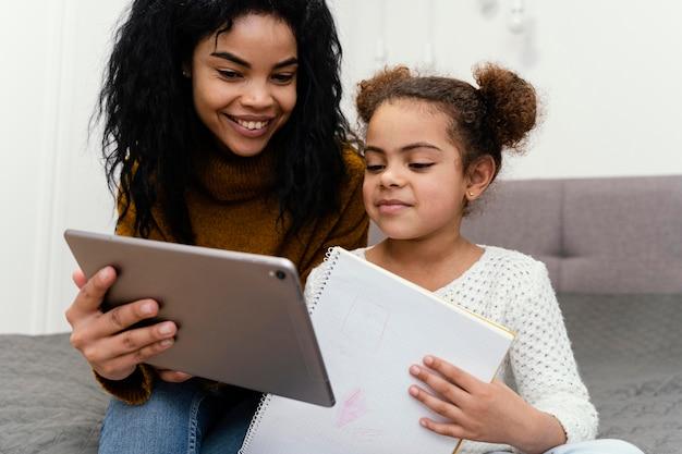 Teenager-mädchen hilft schwester mit tablet für online-schule