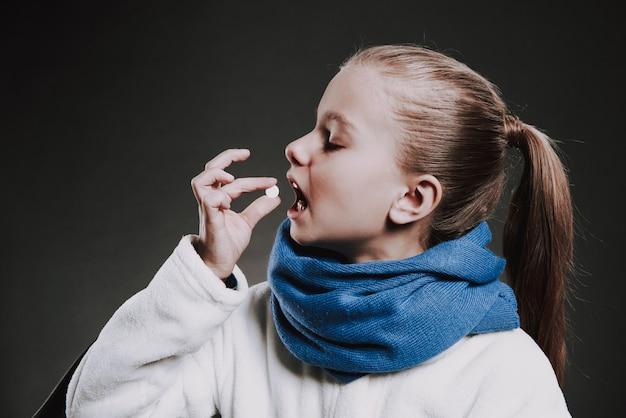 Teenager-mädchen im gestrickten schal setzt pille in den mund.