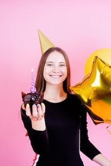 Teenager-mädchen im goldenen geburtstag, der muffin mit kerzen hält und einen wunsch über rosa hintergrund macht