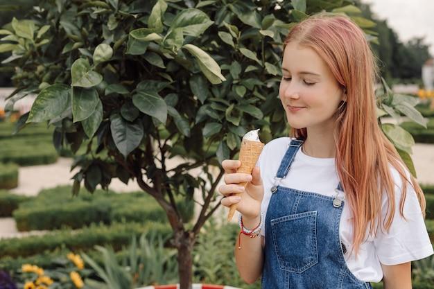 Teenager-mädchen im jeanskleid isst eiscreme heißen sommertag, foto