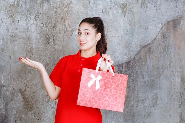 Teenager-mädchen im roten hemd, das eine rote einkaufstasche hält und auf jemanden zeigt.