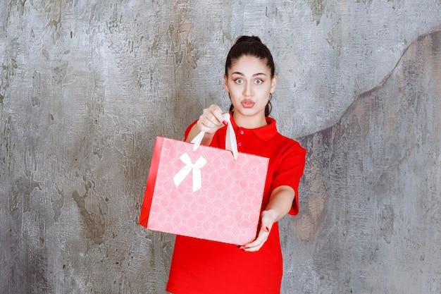 Teenager-mädchen im roten hemd hält eine rote einkaufstasche und präsentiert sie