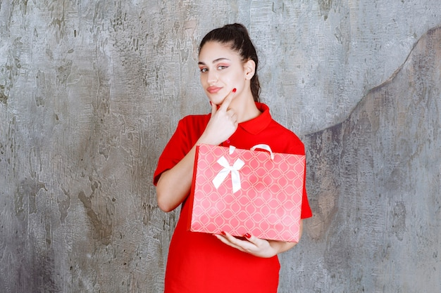 Teenager-mädchen im roten hemd mit einer roten einkaufstasche und sieht verwirrt und nachdenklich aus.