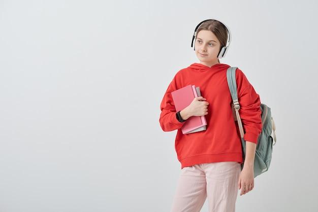 Teenager-mädchen im roten kapuzenpulli und in den weißen jeans, die bücher durch brust halten und ihre lieblingsmusik in kopfhörern isoliert hören