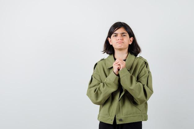 Teenager-mädchen in armeegrüner jacke, die sich die hände in betender geste umklammert und düster aussieht, vorderansicht.