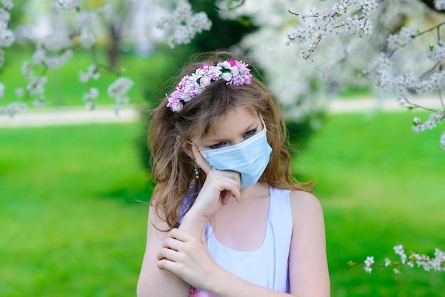 Teenager-mädchen in der medizinischen maske im blühenden garten des frühlings. konzept der sozialen distanz, prävention von coronavirus.