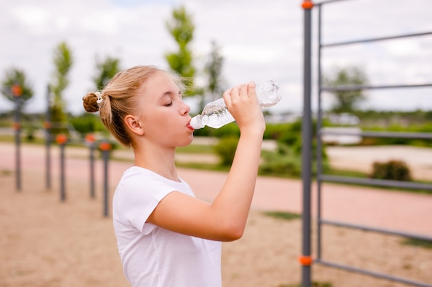Teenager-mädchen in der uniform, die auf dem sportplatz ausarbeitet und klares wasser von einer klaren flasche trinkt.
