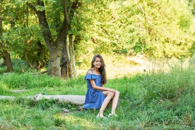Teenager-mädchen in einem blauen kleid geht in den sommerwald bei sonnenuntergang