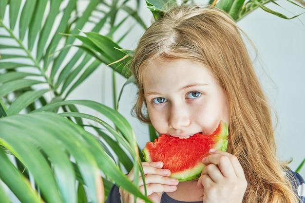 Teenager-mädchen in einem blauen kleid mit tupfen, die eine wassermelone essen.